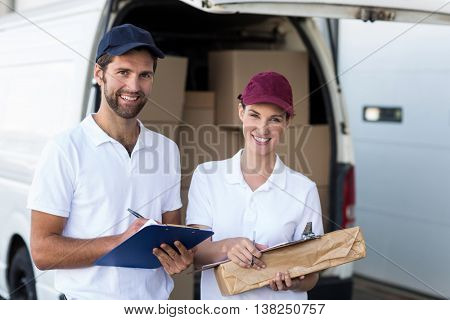 Portrait of delivery people are holding goods and smiling to the camera in front of a wraehouse