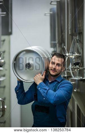 Portrait of happy brewer carrying keg at brewery
