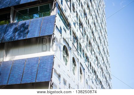 Solar panels attached to the wall of a modern office building on a sunny day with blue skies