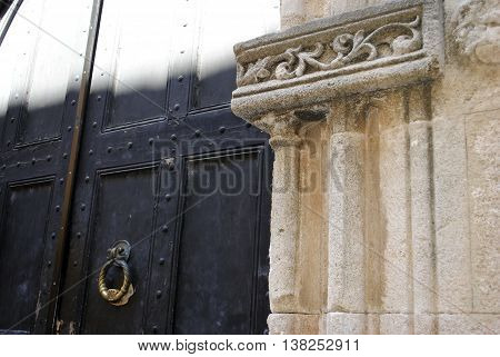 antique doors into the courtyard with a decorative column fragment