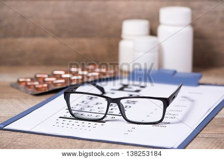Healthy eyes. Eye chart and medicine on wood plank