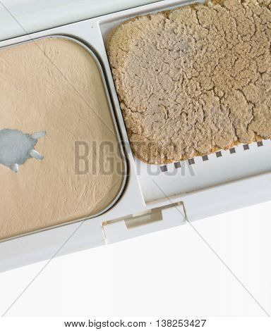 Used press powder make up and dirty puff in case isolated on white background