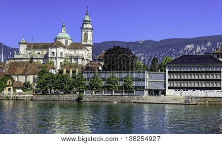Solothurn, Switzerland - 10 July, 2016: buildings on the Ritterquai quay of the Aare river with towers of the St. Ursus Cathedral in the background. The city of Solothurn is the capital of the Swiss Canton of Solothurn.