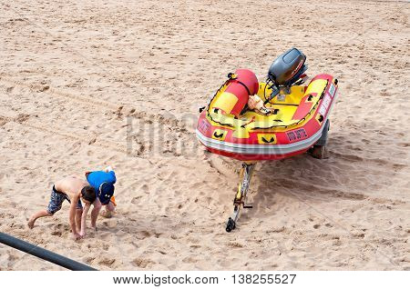DURBAN SOUTH AFRICA - JULY 09 2016: Children playing on the beach near a surf rescue boat in Umhlanga Rocks