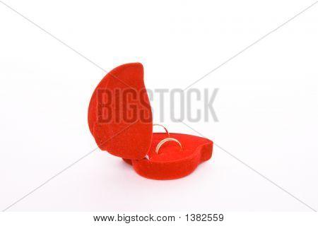 On White Background Rear View Wedding Rings In Red Heart Shaped Velvet Box