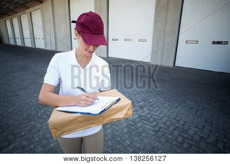 Portrait of delivery man is writing something on a clipboard in front of a warehouse