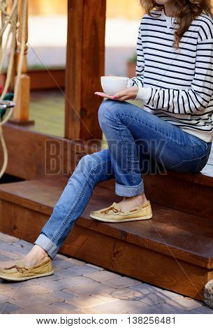 Cup Of Coffee In Hands Woman Which Sits On The Wooden Steps