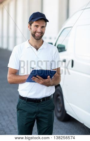 Portrait of delivery man is holding a clipboard and smiling to the camera next to his van