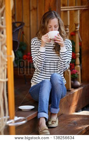 Young Woman Drinking Coffee Or Tea Sitting On The Porch