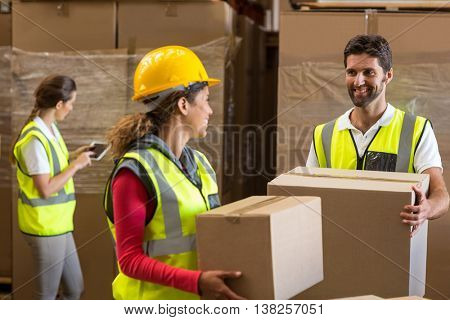 Portrait of workers are holding cardboard boxes and looking each other in a warehouse