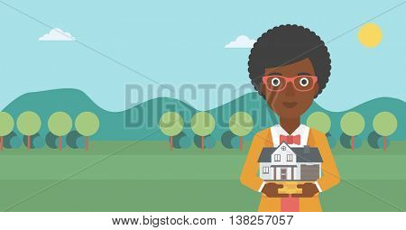 Young woman holding house model in hands on the background of mountains. Real estate agent with house model in hands. Vector flat design illustration. Horizontal layout.