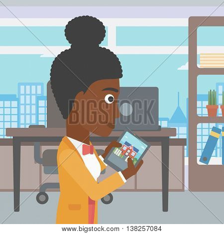 An african-american woman looking at house on a digital tablet screen. Young woman standing in office and looking for house on tablet computer. Vector flat design illustration. Square layout.