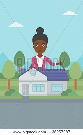 An african-american woman standing behind the house and showing thumb up. Female real estate agent offering the house. Young woman giving thumb up. Vector flat design illustration. Vertical layout.