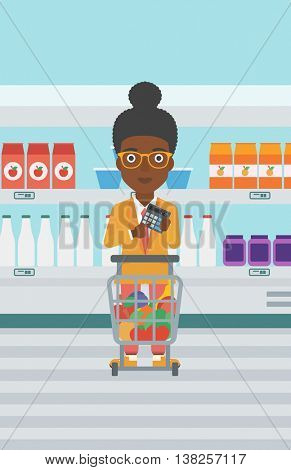 An african-american woman at the supermarket with calculator and supermarket trolley full with products. Woman checking prices with calculator. Vector flat design illustration. Vertical layout.