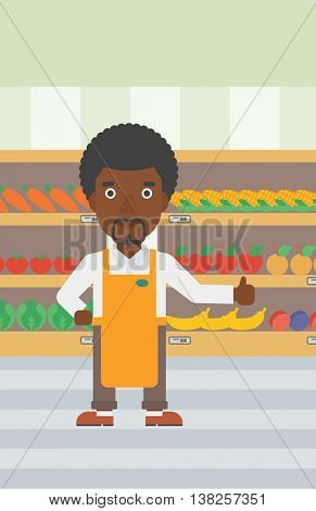 An african-american male supermarket worker showing thumb up on the background of shelves with vegetables and fruits in supermarket. Vector flat design illustration. Vertical layout.