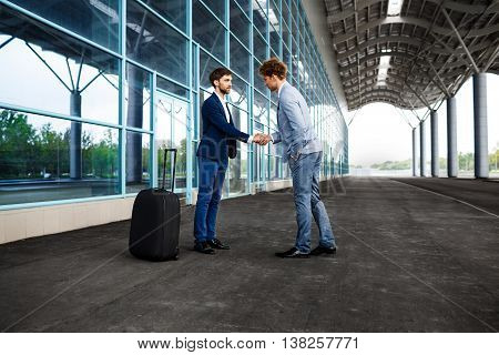 Picture of  two young businessmen talking on street background and shake hands