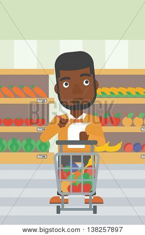 An african-american thoughtful man standing at the supermarket with supermarket trolley full with products and holding a shopping list in hands. Vector flat design illustration. Vertical layout.