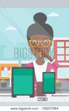Astonished woman looking at digital tablet and smartphone through shop window. An african-american woman with open mouth looking at tablet and phone. Vector flat design illustration. Vertical layout.