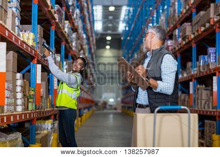 Worker and manager smiling and looking each other in a warehouse
