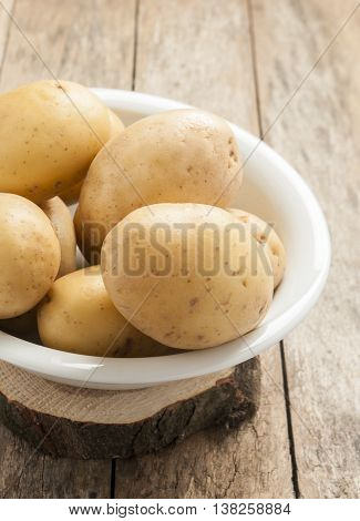 Raw uncooked potatoes on wooden background with copy space