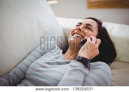 Smiling woman talking on phone while lying down on sofa at home