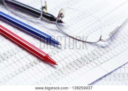 Business concept. Closeup of three colored pens near spectacles on paper with digits