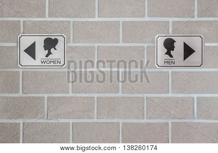 Closeup aluminum toilet sign for woman and aluminum toilet sign for man on brick wall textured background