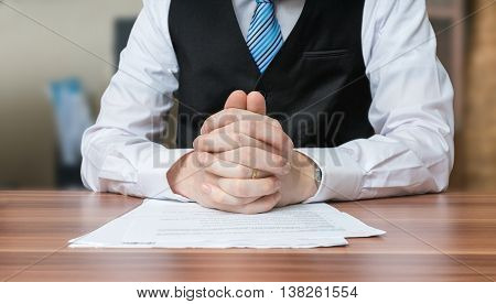 Politician With Clapsed Hands Sitting Behind Desk.