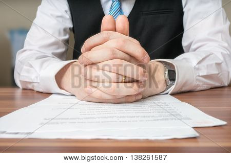 Negotiation With Lawyer Who Is Sitting Behind Desk And Has Clasp
