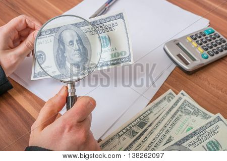 Viewing fake or counterfeit dollar banknote with magnifying glass.