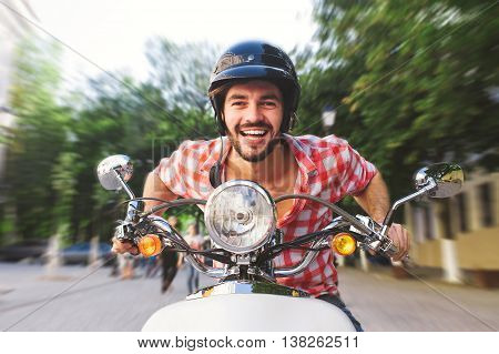 Handsome man riding a scooter on city streets on summer day. Closeup portrait of happy smiling bearded young male on vintage scooter with motion blur