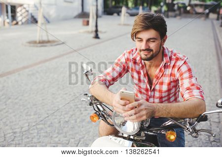 Smiling young man texting on the cellphone while sitting on a scooter on a summer day