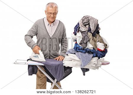 Cheerful senior man ironing a pile of clothes on an ironing board isolated on white background