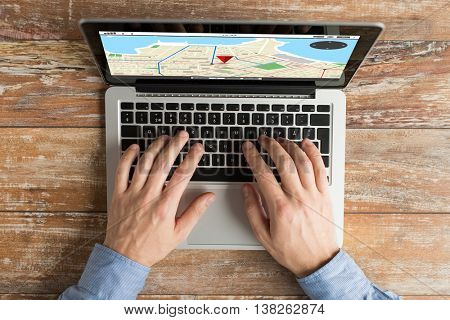 business, location, navigation, people and technology concept - close up of male hands typing on laptop computer with gps navigator map on screen keyboard on table