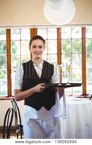Portrait of waitress holding serving tray with champagne flutes in restaurant