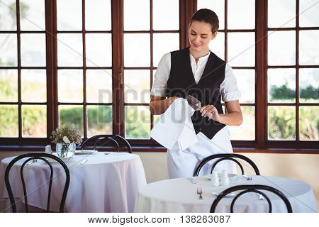 Smiling waitress cleaning wine glass in restaurant