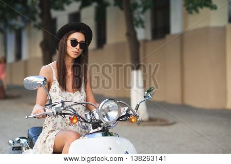 Young beautiful italian woman sitting on a italian scooter. Fashion hipster girl wearing black sunglasses and stylish hat riding a scooter on city streets