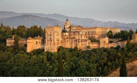 Closeup of Granada and the ancient arabic fortress of Alhambra at dusk with Sierra Nevada in the background. Spain.