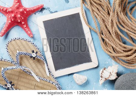 Beach vacation background. Flip-flops, seashells and blackboard for your text over stone backdrop. Top view with copy space