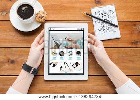 business, internet shopping, technology and people concept - close up of woman with online shop web page on tablet pc computer screen, notebook and coffee on wooden table