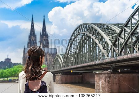 Young woman seen from back looking to rhine river, huge bridge and famous cathedral of Cologne, Germany