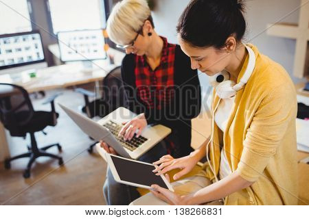 Two female graphic designer using digital tablet and laptop in office
