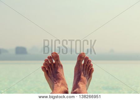 summer holidays, beach, travel, leisure and body care concept - closeup of male feet over sea and sky