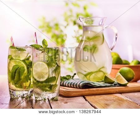 Country drink. On wooden boards is glass jug with transparent drink and lime glue bowl. Drink number hundred fifty with ice cubes on checkered napkin. Country life. Light background.