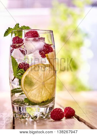 Alcohol drink. On wooden boards is glass with alcohol drink and ice cubes. A drink number hundred seventeen cocktail raspberry mojito and lime with mint berry. Country life. Outdoor. Light background.
