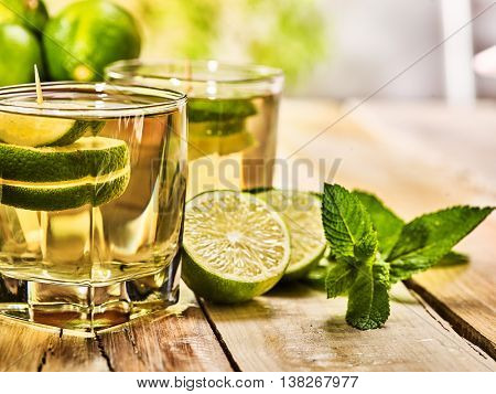 Country drink. Wooden boards are half two glasses with green transparent drink and lime glue bowl. Drink number hundred forty eight mojito with mint leaf on sunlight . Country life. Light background.