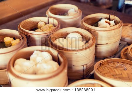 cooking, asian kitchen, sale and food concept - meat or rice balls in wooden containers