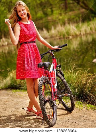 Bicycle girl. Girl with long hair wearing red polka dots dress rides bicycle into park. Girl in ecotourism. Bicycle is good for health. Bicycle girl is happy.