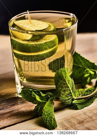 Alcohol drink. On wooden boards is glass with alcohol green transparent drink. A drink number hundred forty seven mohito cocktail with lime. Country life. Black background.