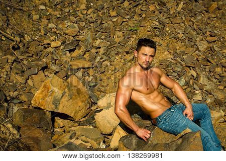 handsome young macho man with muscular sexy body and six packs on torso in jeans sunny day outdoor on stony natural background